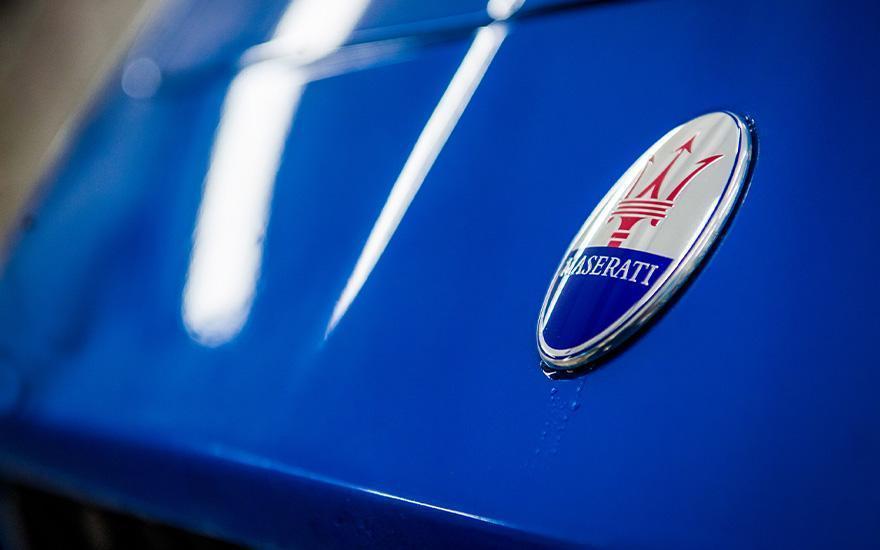 emblemat Maserati naniebieskiej karoserii