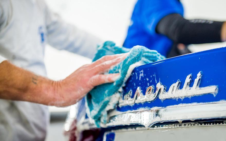 specjaliści czyszczący karoserię samochodu